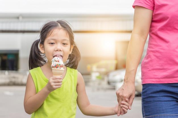 Meisje dat en de linkerhandholding glimlacht eet hand haar moeder