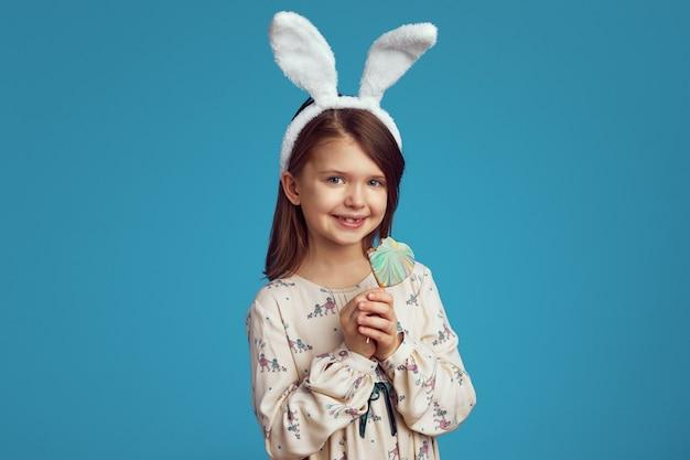 Meisje dat en een koekje in vorm van hart glimlacht houdt dat konijntjesoren draagt