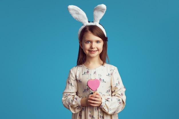 Meisje dat en een koekje in vorm van hart glimlacht houdt over blauwe muur