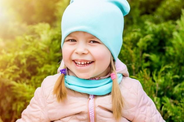 Meisje dat en in het park op het gras lacht glimlacht