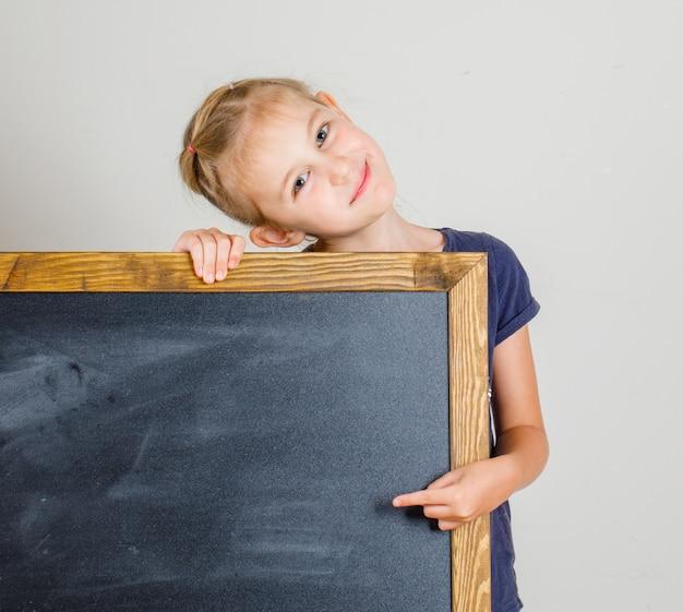 Meisje dat en op bord in t-shirt vooraanzicht glimlacht richt.