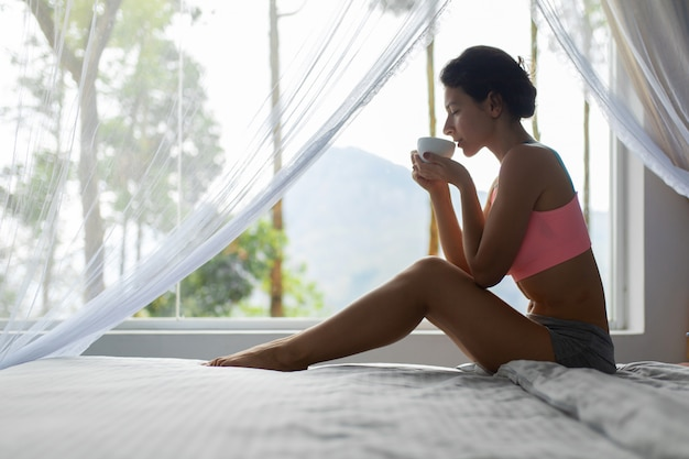 Meisje dat en thee in bed met uitzicht op de berg op het eiland sri lanka rust drinkt
