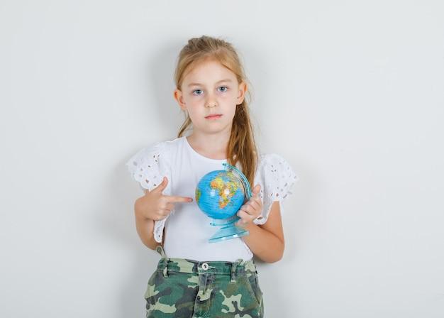 Meisje dat ergens op wereldbol in wit t-shirt toont