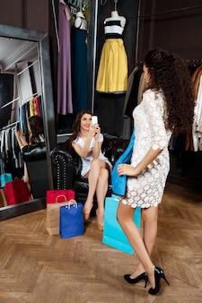 Meisje dat foto neemt van een ander die kleding in wandelgalerij probeert.