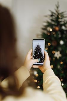 Meisje dat foto's neemt op de kerstboom van de telefoon