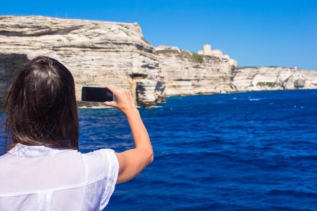 Meisje dat foto's op een telefoon in bonifacio, corsica, frankrijk neemt
