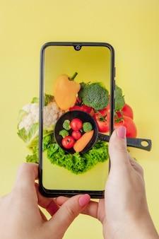 Meisje dat foto van vegetarisch voedsel op tafel met haar smartphone. veganistisch en gezond concept.