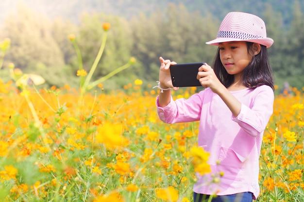 Meisje dat fotomobiele telefoons op bloemengebied neemt
