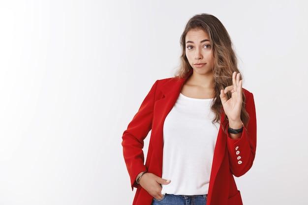 Meisje dat geen slecht gebaar toont. onder de indruk vrouwelijke collega die een goed teken maakt en er respectvol uitziet en een geweldig resultaat bekijkt, zoals verbaasd, een rood jasje aan en een witte muur