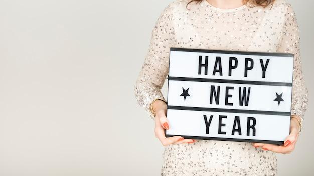Meisje dat gelukkig nieuw jaarteken houdt