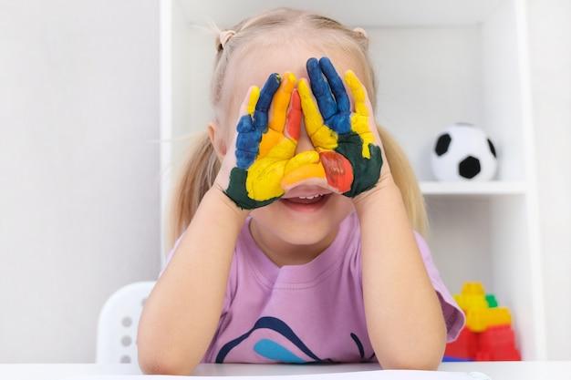 Meisje dat geschilderde handen toont. handen geschilderd in kleurrijke verf. ogen gesloten met handpalmen
