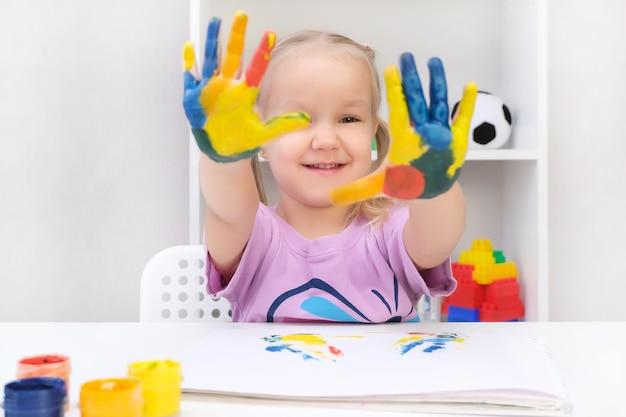 Meisje dat geschilderde handen toont. handen geschilderd in kleurrijke verf. onderwijs, school, kunst en schilderconcept