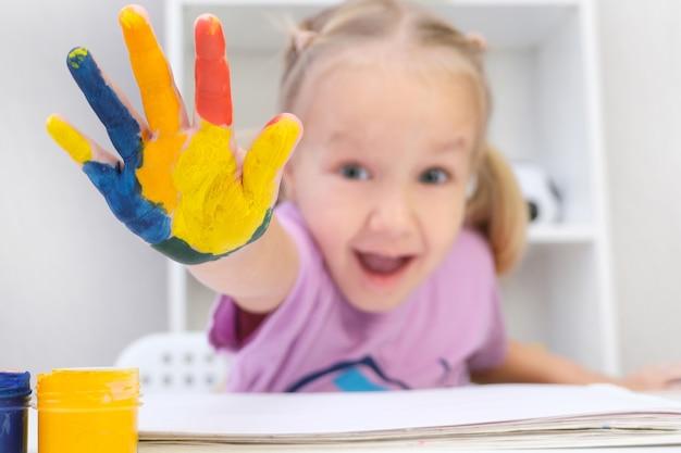 Meisje dat geschilderde handen toont. handen geschilderd in kleurrijke verf