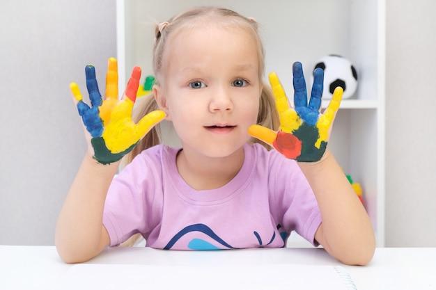 Meisje dat geschilderde handen toont