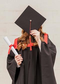 Meisje dat gezicht behandelt met graduatiehoed