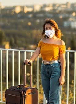 Meisje dat gezichtsmasker met koffer in park draagt. reizen tijdens pandemie