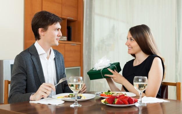 Meisje dat gift geeft tijdens romantisch diner