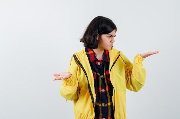 Meisje dat grootteteken toont in gecontroleerd overhemd, jasje en peinzend kijkt