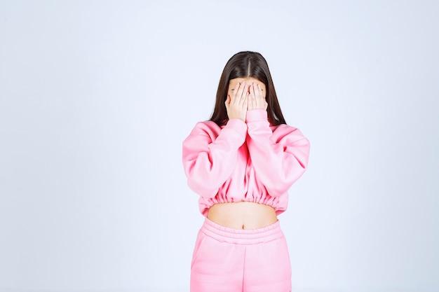 Meisje dat haar gezicht met haar hand verbergt