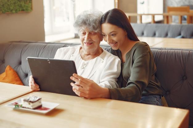 Meisje dat haar grootmoeder onderwijst hoe een tablet te gebruiken