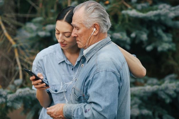 Meisje dat haar grootvader leert hoe een telefoon te gebruiken