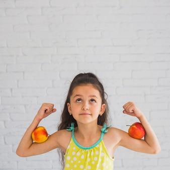 Meisje dat haar handen buigt die appel op haar bicepsen houden die omhoog eruit zien