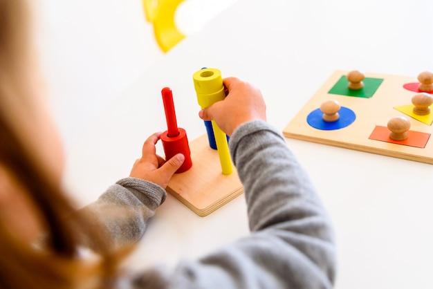 Meisje dat haar handvaardigheid ontwikkelt met een zintuiglijk materiaal van kleuren.
