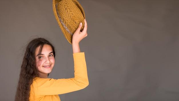 Meisje dat haar hoed met exemplaarruimte steunt