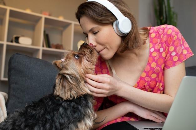 Meisje dat haar hond kust en aan muziek luistert