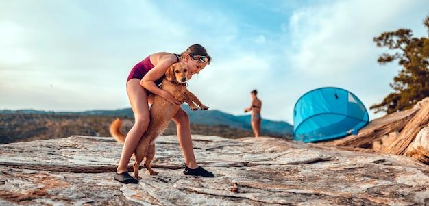 Meisje dat haar hond omhelst bij het rotsachtige strand