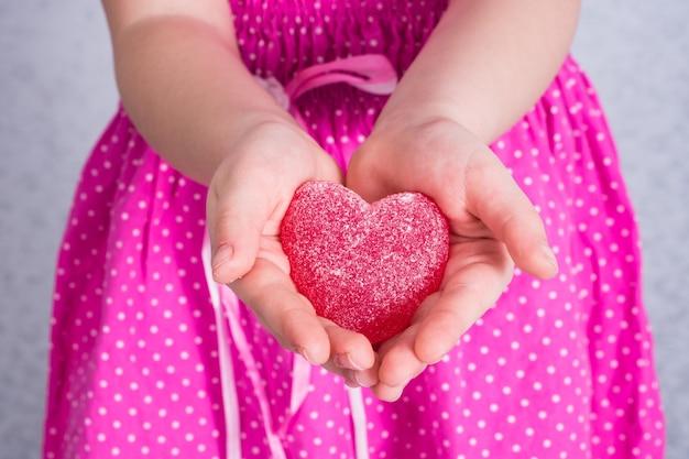 Meisje dat haar marmeladehart in haar handpalmen uitrekt