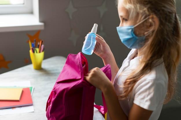 Meisje dat haar ontsmettingsmiddel op haar rugzak zet