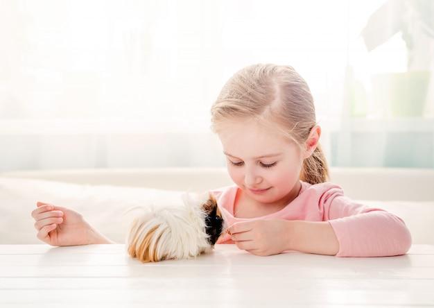 Meisje dat haar proefkonijn voedt
