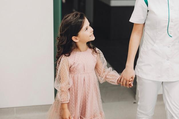 Meisje dat haar tandarts bezoekt. snoepje hand in hand lopen voor tandonderzoek.