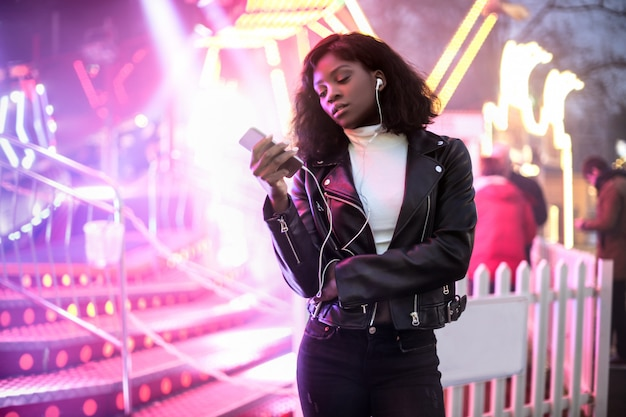 Meisje dat haar telefoon controleert terwijl het lopen in lunapark