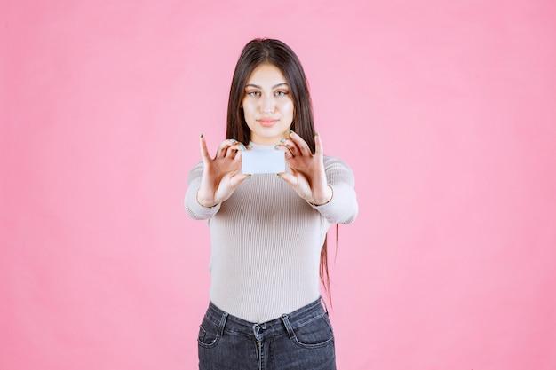 Meisje dat haar visitekaartje voorstelt aan een zakenpartner