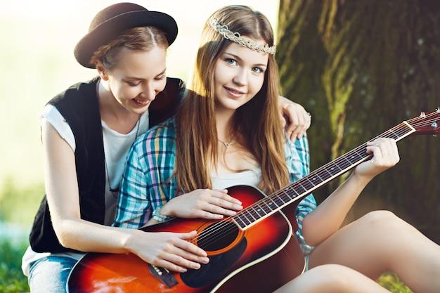 Meisje dat haar vriend leert om gitaar te spelen in het park