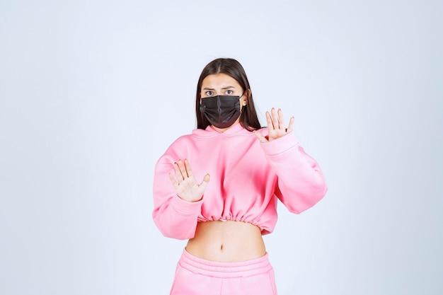 Meisje dat haar zwarte masker draagt en het virus tegenhoudt.