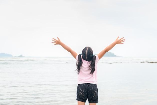 Meisje dat handen op het strand, vrijheid opheft