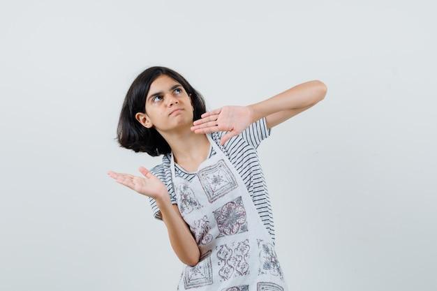 Meisje dat handen opheft om zich in t-shirt, schort te verdedigen en bang te kijken