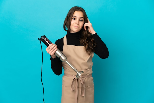 Meisje dat handmixer gebruikt die op blauwe muur wordt geïsoleerd die een idee denkt