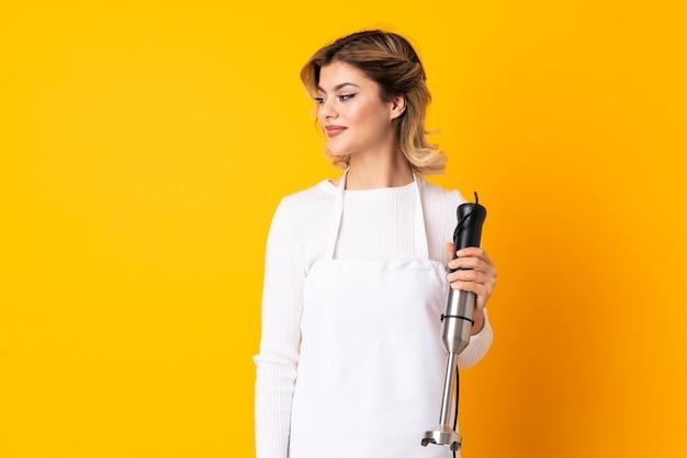 Meisje dat handmixer gebruikt die op gele muur wordt geïsoleerd die kant kijkt