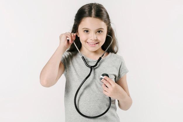 Meisje dat hartslag met stethoscoop onderzoekt