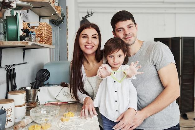 Meisje dat hartvormige kokende vorm toont. bij de tafel in de keuken. leuke familie poseren voor de foto