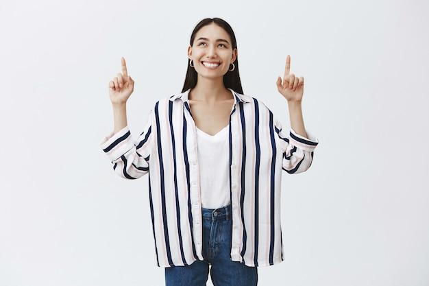 Meisje dat hemel bekijkt die van warm zonnig weer geniet. aantrekkelijke onbezorgde vrouwelijke student in gestreepte blouse en jeans, die en met brede gelukkige glimlach omhoog kijkt, die zich over grijze muur bevindt