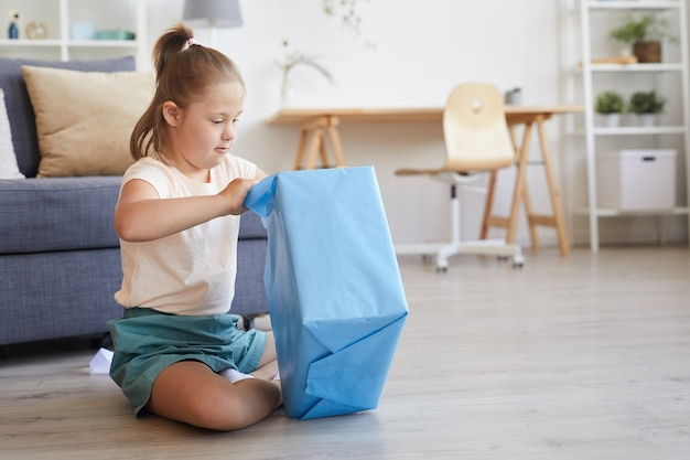 Meisje dat het grote cadeau opent terwijl ze op de vloer in de kamer zit