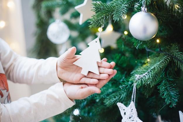 Meisje dat het huis met kerstboom en kerstmisdecor verfraait.