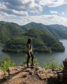 Meisje dat het landschap van het bergmeer overziet in tarnita, transsylvanië, roemenië