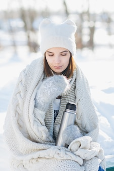 Meisje dat hete thee drinkt van een thermosfles