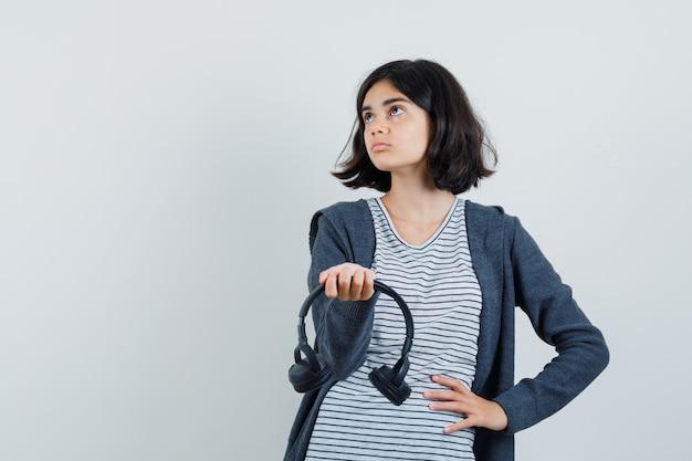 Meisje dat hoofdtelefoons in t-shirt, jasje presenteert en gericht kijkt.
